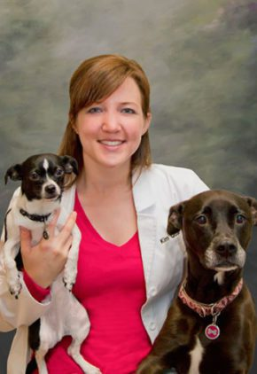 Dr. Kim Egeler is board certified in small animal surgery. She is sitting with a small black and white dog and a large brown dog.