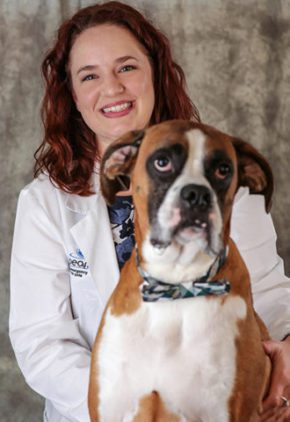 Dr. Sloane Everett is a resident in our cardiology service. She is sitting with a large brown and white dog.