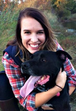 Dr. Emily Davis is an emergency medicine veterinarian. She is hugging a black dog with its tongue out.