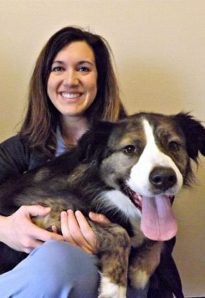 Dr. Heather Newton is an emergency medicine veterinarian. She is holding a dog on her lap.