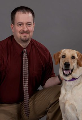 Dr. Richmond Aarstad is a clinician in our emergency medicine service. He is sitting next to a yellow lab.