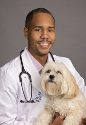 Dr. Forrest Cummings is a veterinarian board certified in small animal internal medicine. He is holding a medium-sized blond dog.