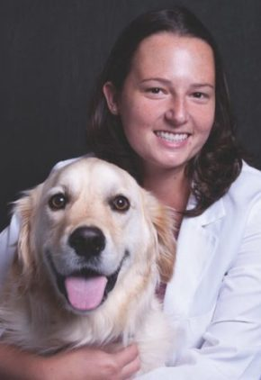 Dr. Kelly Kezer is board certified in veterinary oncology. She is sitting with a golden retriever.
