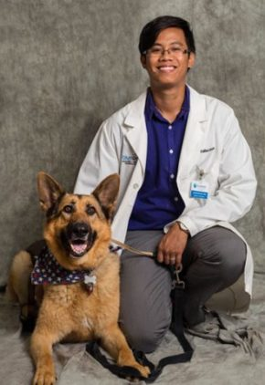 Dr. Laison Nguyen is a resident in our ophthalmology service. He is kneeling next to a large tan and black dog.