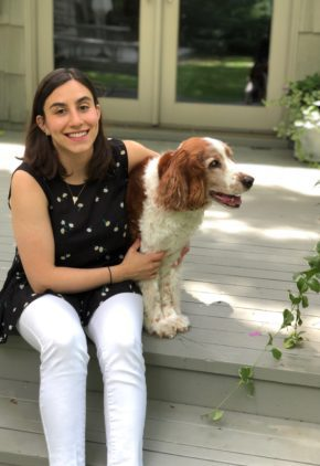 Dr. Sabrina Katz is an emergency medicine veterinarian. She is sitting on a porch with a red and white dog.