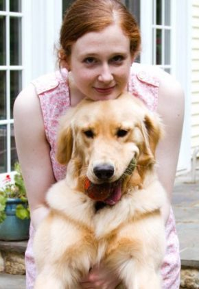 Dr. Caitlin Barry-Heffernan is board certified in veterinary internal medicine. She is holding a golden retriever in her arms.