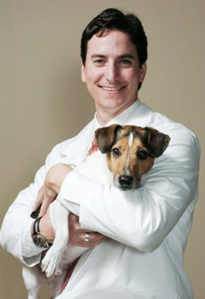 Dr. Eric Bulakowski is board certified in veterinary oncology. He is holding a small dog in his arms.