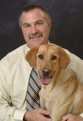 Dr. Kyle Kerstetter is board certified in veterinary surgery. He is sitting with a large blond dog.
