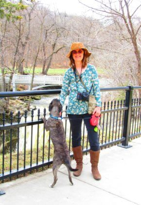 Anastasia Bamford is a certified veterinary technician and board certified in veterinary emergency and critical care medicine. She is outside on a bridge, which her dog is looking over.