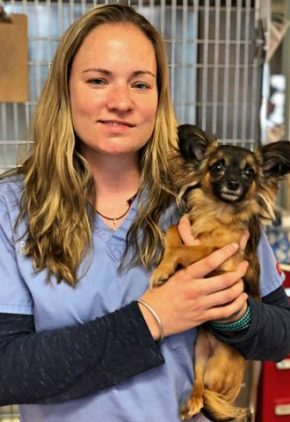 Dr. Meghan Respess is board certified in veterinary emergency and critical care medicine. She is holding a small, long-haired dog.