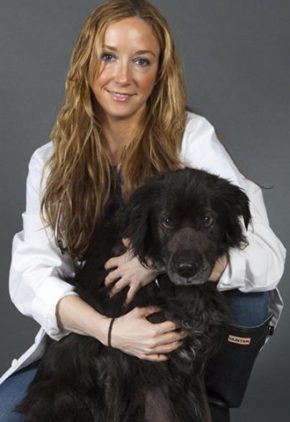 Dr. Meredith Daly is board certified in veterinary emergency and critical care medicine. She is hugging a long-haired black dog.