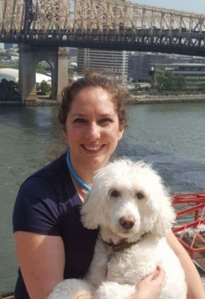 Dr. Lauren Wiley is board certified in veterinary cardiology. She is sitting outside by a bridge with a white fluffy dog.