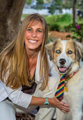 Dr. Natalie Goolik is a doctor in our emergency medicine service. She is sitting with a white long-haired dog wearing a tie.