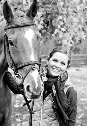 Dr. Bridget Urie is board certified in veterinary oncology. She is outside holding onto her horse.