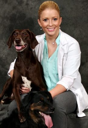 Dr. Hope Chisnell is board certified in small animal surgery. She is hugging a large brown dog.