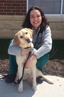 Dr. Rachel Smith is board certified in veterinary internal medicine. She is outside hugging a yellow lab.