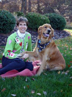 Dr. Rebecca Miller is an emergency medicine veterinarian. She is sitting in the grass with a golden retriever who has his paw on her hand.