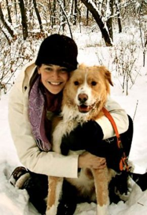 Dr. Rebecca Rittenberg is a resident in our internal medicine service. She is sitting in the snow hugging a tan and white long-haired dog.