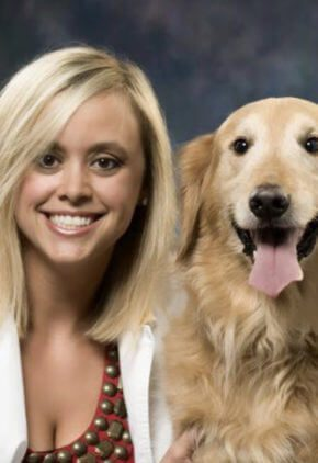 Dr. Laura Loftin is an emergency medicine veterinarian. She is sitting with a golden retriever.