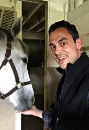 Dr. Nick Szigetvari is board certified in veterinary oncology. He is feeding a white horse from his hand.
