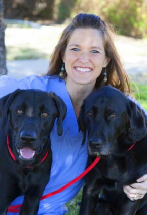 Brooke Clark is board certified in veterinary emergency and critical care medicine. She is outside with two black labs.