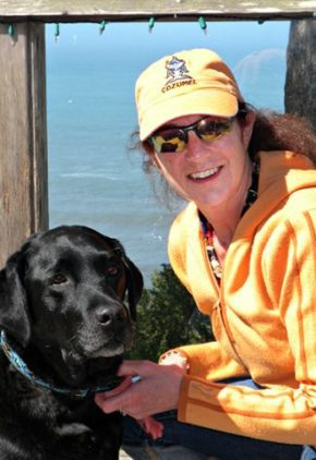 Dr. Deborah Hodesson is a veterinarian in our dentistry service. She is outside by the water with a black lab.