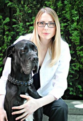 Dr. Jennifer Reagan is board certified in small animal surgery. She is sitting outside with a black great Dane.