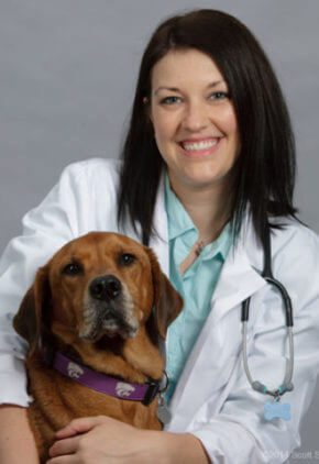 Dr. Carly Waugh is board certified in veterinary internal medicine. She is sitting with a brown dog.