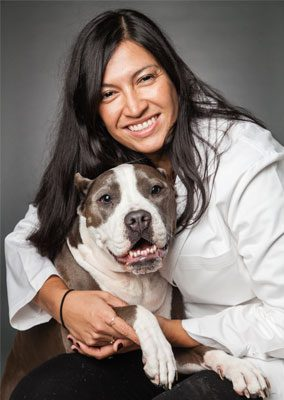 Dr. Michelle Griego-Valles is board certified in veterinary emergency and critical care medicine. She is hugging a large gray and white dog.