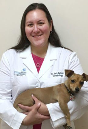 Dr. Judy Seltzer is board certified in veterinary dermatology. She is holding a small tan dog in her arms.